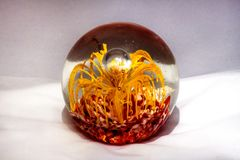 Glass ball. With yellow and red decorative elements in it Royalty Free Stock Image
