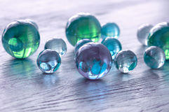 Glass balls of blue and green on a wooden surface. Royalty Free Stock Images