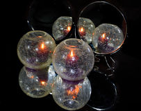 Glass balls. With the candle in the mirror Stock Photo