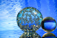 Glass balls in front of blue water Stock Images