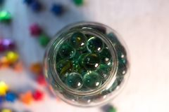Glass balls in a glass jar with a blurred background. Glass balls in a glass jar with a blurred background stock photo
