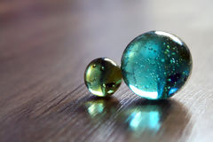 Glass balls. Two glass balls together in a wooden floor Stock Photography