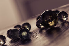 Glass balls on a wooden surface at an angle. Stylish artistic work. Selective focus. royalty free stock photo