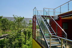 Glass-balustraded steel stairs to roof of container-made buildin. Glass-balustraded steel stairs to the roof of a container-made building in sunny summer,Chengdu Royalty Free Stock Photo