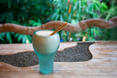 A glass of banana smoothie on a wooden table on green background. Beautiful turquoise glass with fresh banana smoothie and a tube of bamboo on a wooden textured Royalty Free Stock Photos