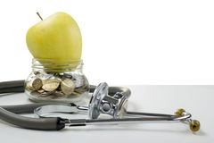 Glass bank with coins, green apple and medical stethoscope. Medi. Cal costs, financial concept Stock Images
