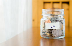 Glass bank for tips with money Stock Photos