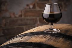 Glass of barrel aged stout. Snifter glass with black stout beer standing on an oak barrel in a cellar Royalty Free Stock Photos