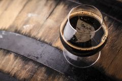 Glass of barrel aged stout. Snifter glass with black stout beer standing on an oak barrel in a cellar Stock Photo