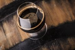 Glass of barrel aged stout. Snifter glass with black stout beer standing on an oak barrel in a cellar Stock Images