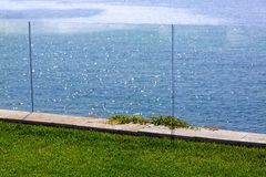 Glass barrier of a green lawn. Glass barrier of a green lawn in the background a panoramic view of the sea on a sunny summer day, nobody royalty free stock photo