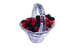 Glass basket full of raspberries and blackberries Stock Images
