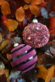 Glass baubles. Traditional Christmas glass baubles on colorful leaves Royalty Free Stock Images