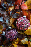 Glass baubles. Traditional Christmas glass baubles on colorful leaves Royalty Free Stock Image