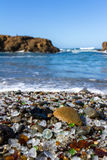 Glass Beach, Fort Bragg, California. Beautiful sea glass in a variety of colors with blue waves and sky in Fort Bragg, California Stock Image