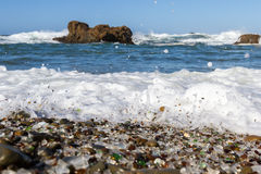 Glass Beach, Fort Bragg, California. Beautiful sea glass in a variety of colors with blue waves and sky in Fort Bragg, California Royalty Free Stock Image