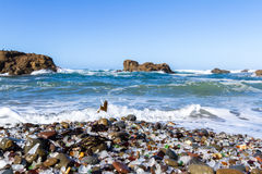 Glass Beach, Fort Bragg, California. Beautiful sea glass in a variety of colors with blue waves and sky in Fort Bragg, California Royalty Free Stock Photo