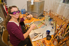 Glass Bead Making. Attractive woman sitting at her work station making glass beads using a propane torch royalty free stock images