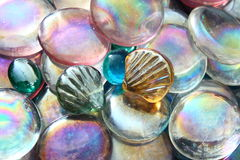 Glass Beads. A pile of glass beads with irridiescent rainbow-like colours. Most are disc shaped but two are in shaped like sea shells Stock Photos