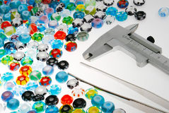 Glass beads and caliper. Colorful glass beads with a pair of tweezers and a Vernier caliper Royalty Free Stock Image