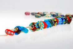 Glass beads on a chain. Handmade colorful glass beads strung on a bracelet or necklace chain Royalty Free Stock Photo