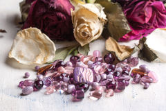 Glass beads with roses. Beautiful glass beads on wite wooden table with dried roses Royalty Free Stock Photo