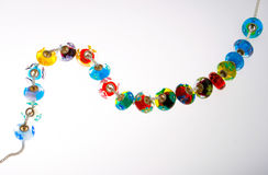 Glass beads on string. Colorful glass beads on a string on a white background Royalty Free Stock Photos