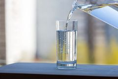 A glass beaker is filled with clean water in the open air. Summer sunny day royalty free stock photos
