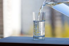 The glass beaker is filled with drinking water. On open air. Summer sunny day royalty free stock photography