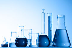 Glass beakers with blue liquid. Various shapes and sizes of glass laboratory beakers filled with blue liquid Royalty Free Stock Photos