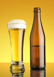 Glass of bear and botte. Glass of beer and bottle on yellow background Royalty Free Stock Photo