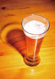 Glass of beer. On a wooden table royalty free stock photography