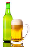 Glass of beer. In the front with foam with green bottle of beer in the back Stock Images