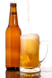 Glass of beer. In the front with foam with bottle of beer in the back Stock Photography