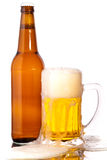 Glass of beer. In the front with foam with bottle of beer in the back stock photo