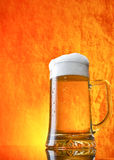 Glass of beer. Close-up with froth over orange background Royalty Free Stock Image