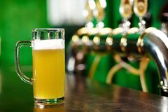 Glass of beer. A beer pint standing on a bar counter not far from beer taps Stock Images