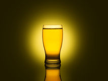 Glass of beer. A glass of beer isolated on a dark and yellow background Royalty Free Stock Photography