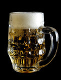 Glass of beer. A glass of fresh beer isolated on a black background stock images
