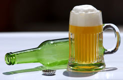 Glass of beer. With empty bottle on a white background and black stock images