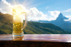 A glass of beer against the backdrop of the Matterhorn in the Sw Royalty Free Stock Photography