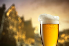 Glass of beer against blurred european city Stock Image