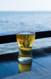 Glass of beer against sea Royalty Free Stock Photography