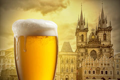 Glass of beer against Tyn Church in Prague