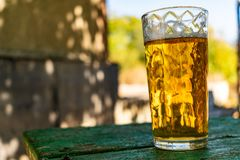 A glass of beer with alcohol. Golden, intoxicating drink in a transparent mug, stands on a wooden stand in the rays of daylight. stock image