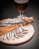 Glass of beer and assorted dried fish on a cooking sheet Stock Photo