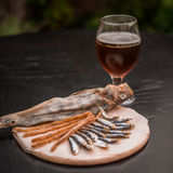 Glass of beer and assorted dried fish on a cooking sheet Royalty Free Stock Photography