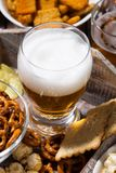 Glass of beer and an assortment of snacks, vertical closeup. Glass of beer and an assortment of snacks, closeup stock photography