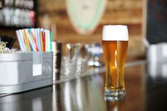 Glass of beer on bar counter in cafe. Glass of beer on bar counter in modern cafe royalty free stock photo