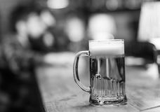 Glass with beer on bar counter, table, visitor on background, defocused. Glass with fresh lager draft beer with foam. Close up. Glass filled with cold tasty Stock Photo